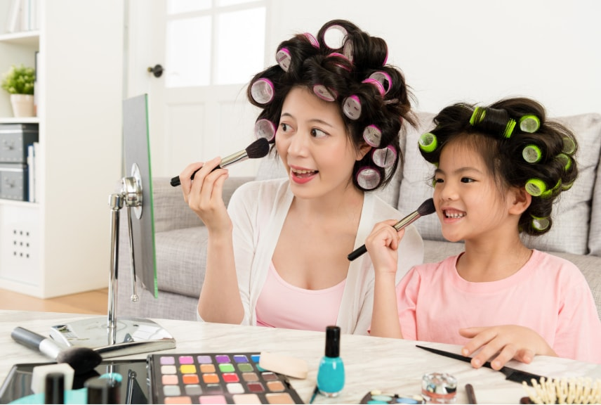 mother and daughter applying makeup with cosmetics brushes